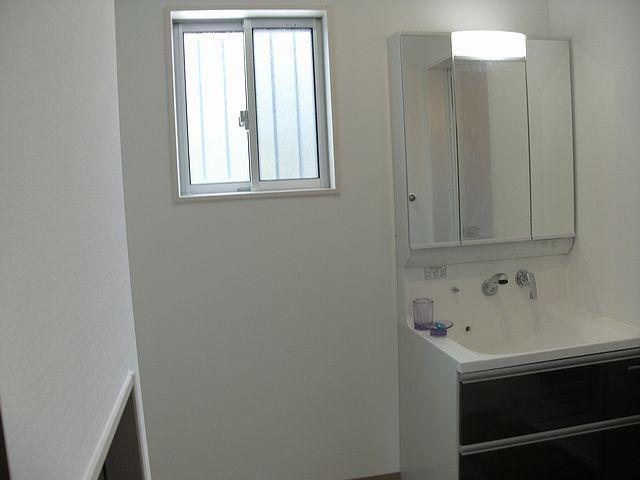 洗面化粧台の横には階段下のデッドスペースを利用した収納があります。