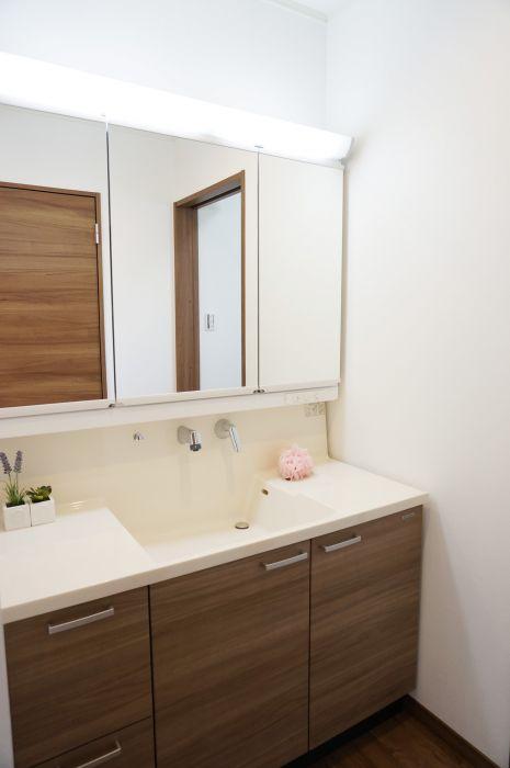 幅広の洗面台は両サイドに物が置けるので便利。ボウルは浸け置き洗いがしやすいスクエア型。水アカが付きにくい壁水栓も嬉しいポイントです。